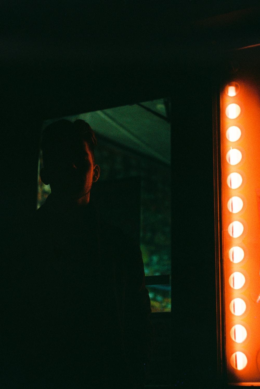 man standing near orange LED sign