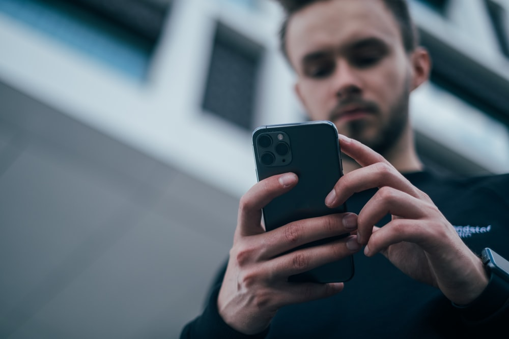 man wearing black sweater using smartphone
