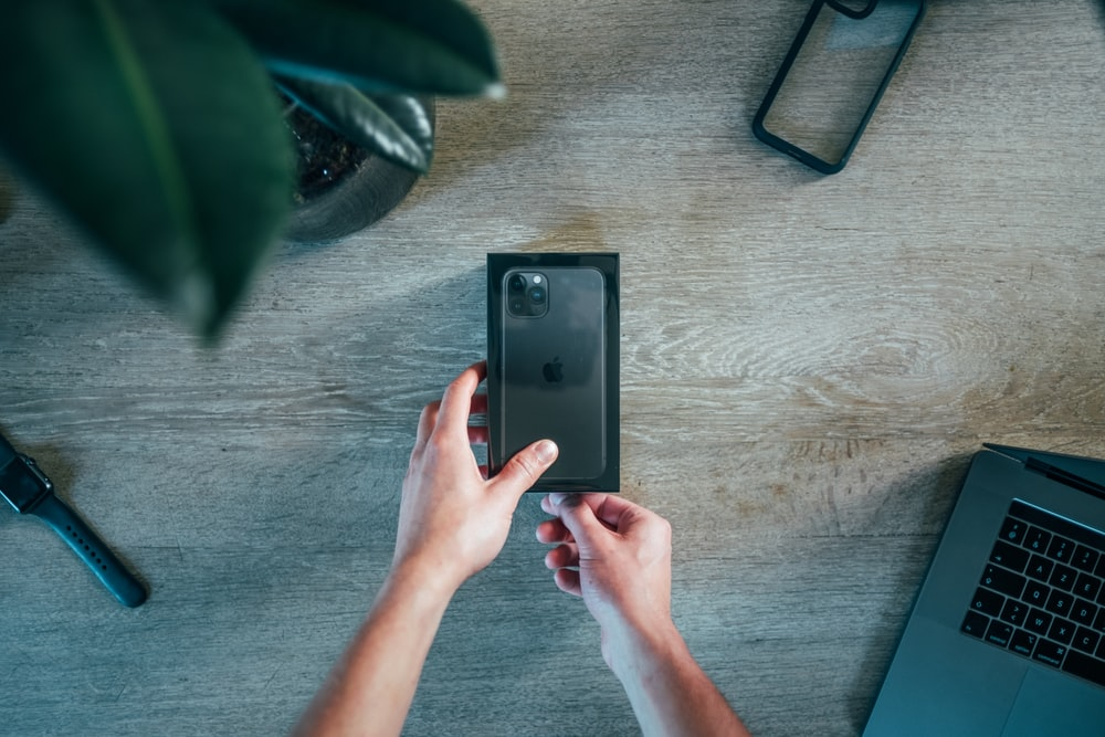 person holding black iPhone 11 box