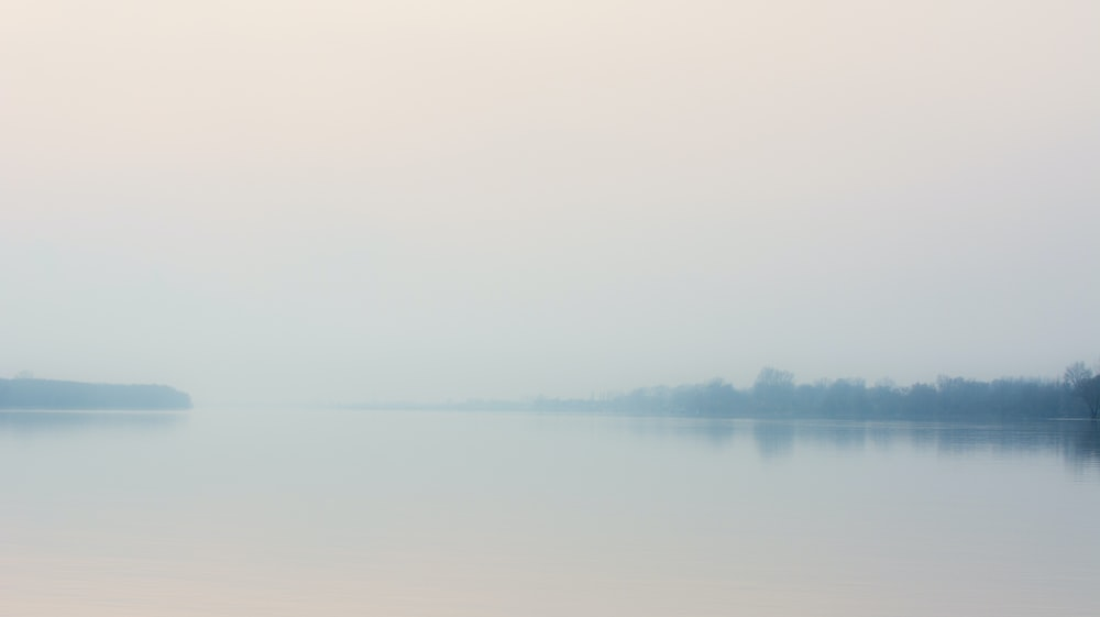 calm body of water under white sky