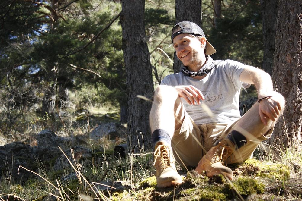 sitting man wearing gray crew-neck t-shirt during daytime