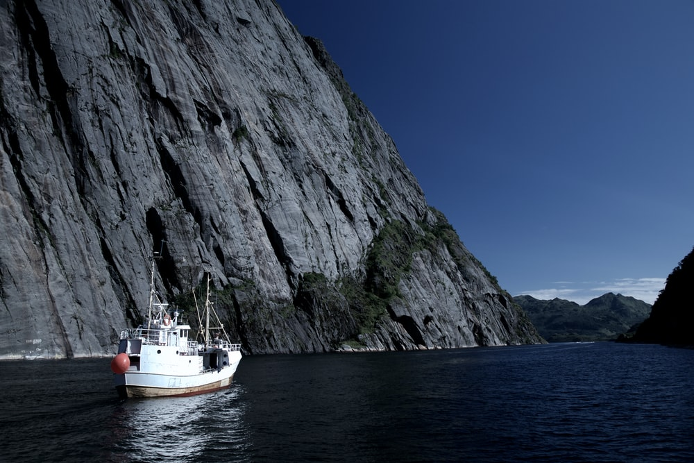 white boat on body of water beside gray cliff