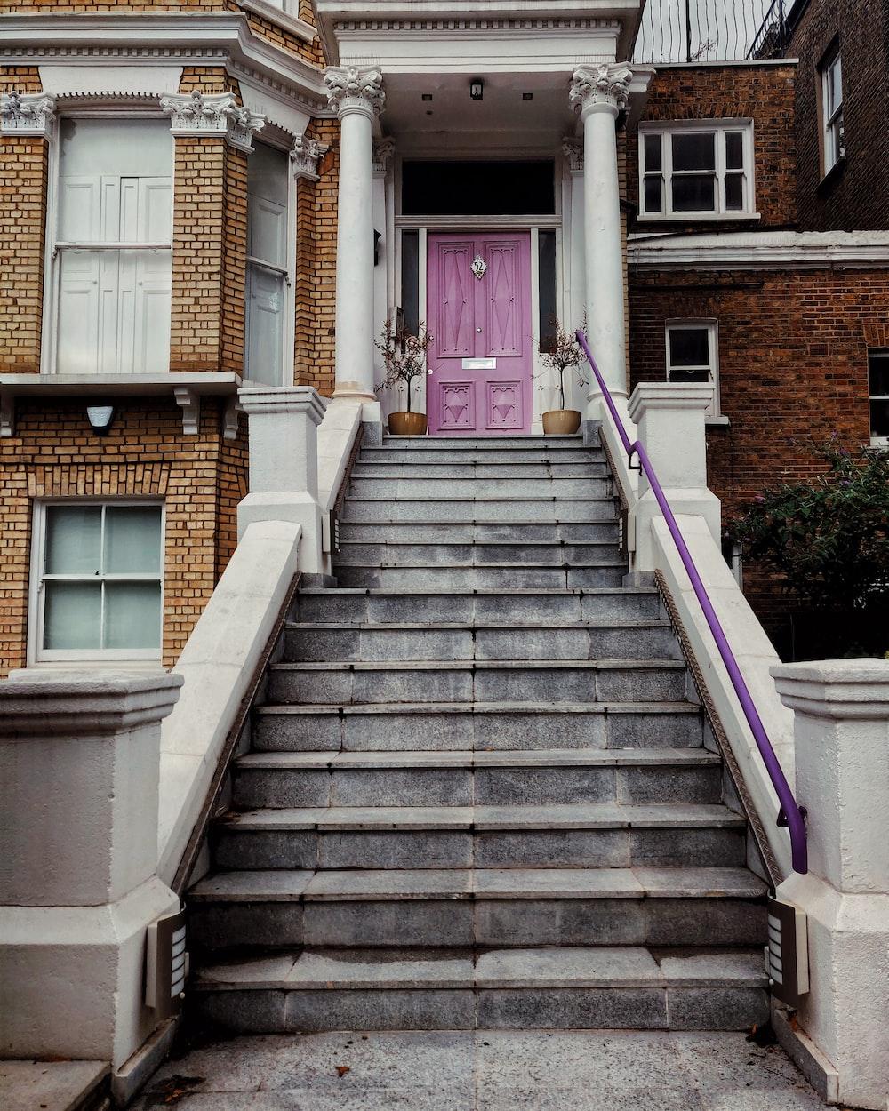 white concrete house showing closed purple wooden door