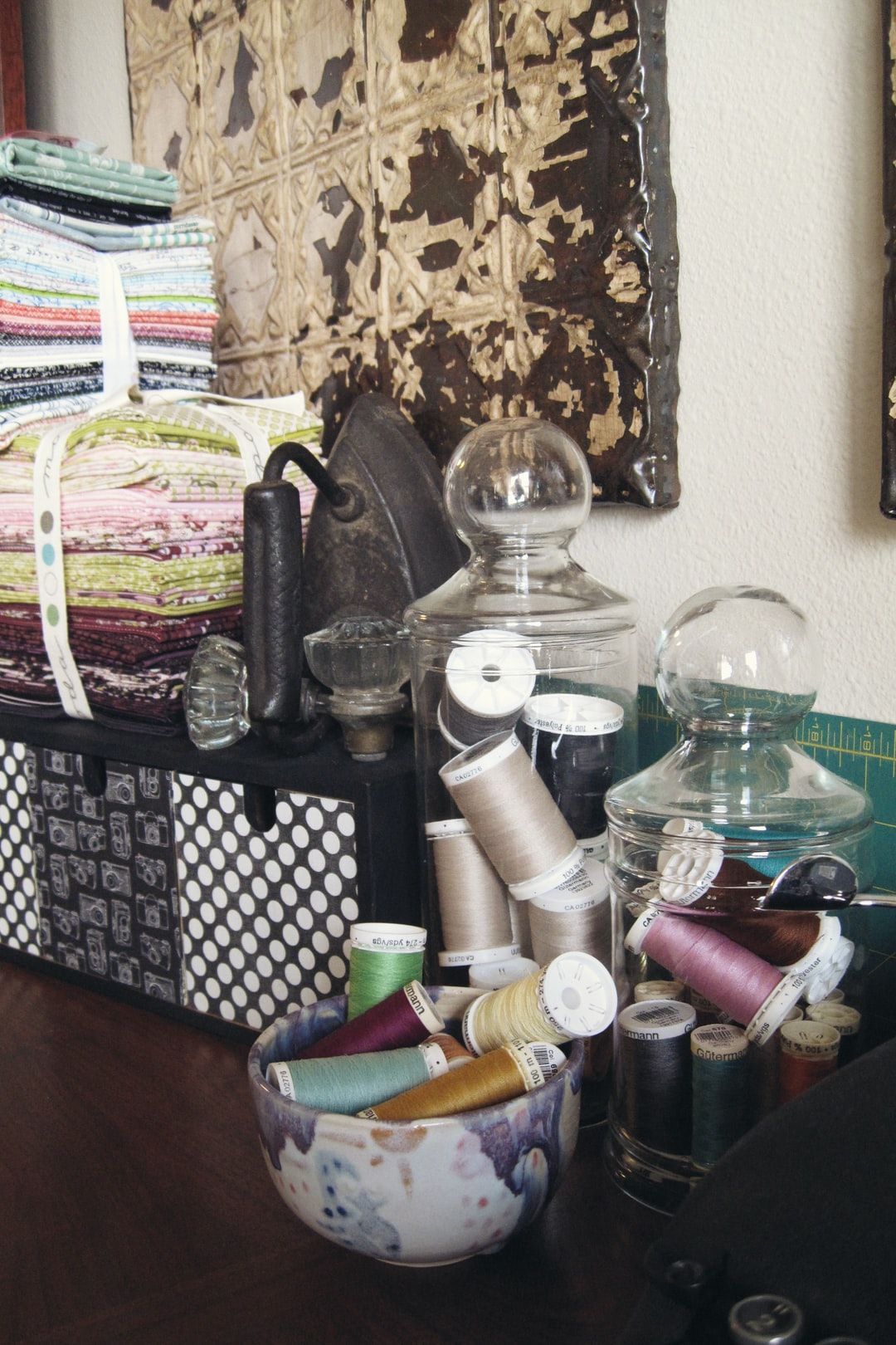 Collection of craft and sewing related supplies, stored on a buffet in clear glass jars and vintage pottery bowls along with stacks of cotton fabric.