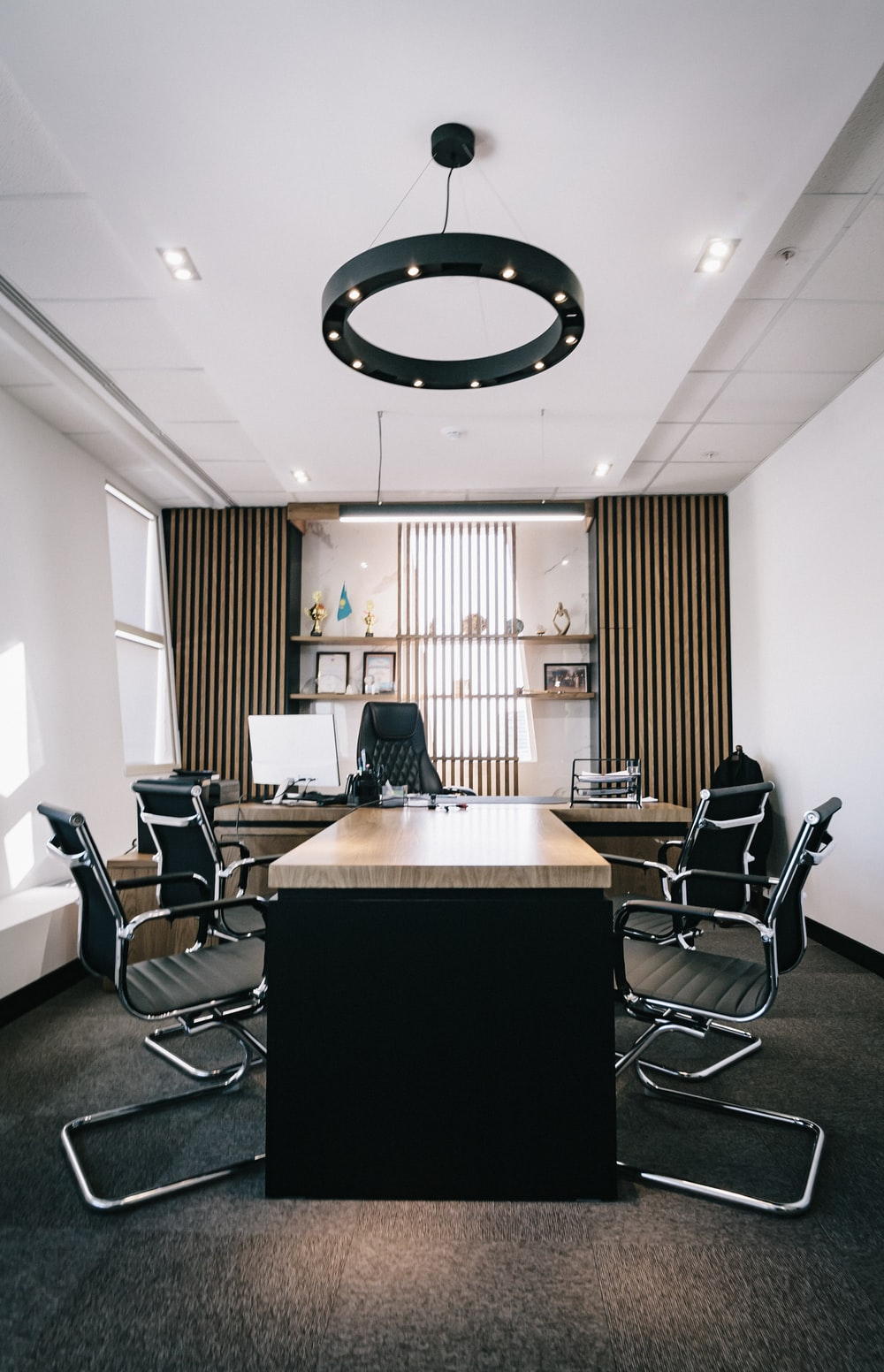 brown and black office table and four black cantilever chairs