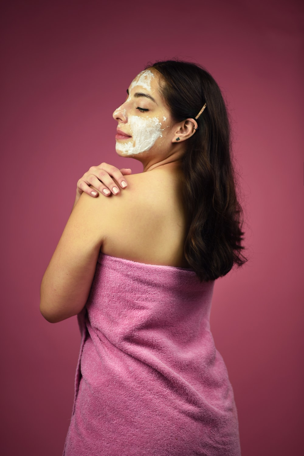 woman looking over her left shoulder wearing pink towel and white cream mask