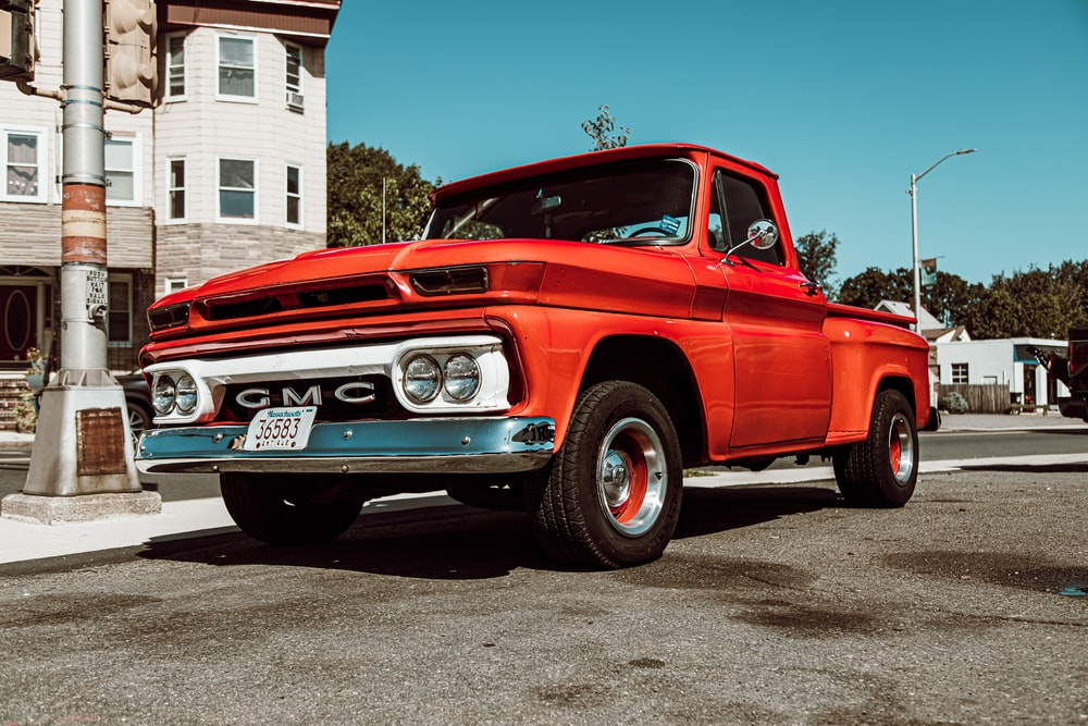 classic red GMC single cab pick up truck on road