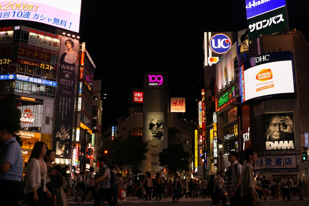 crowd of people walking beside buildings during nightime