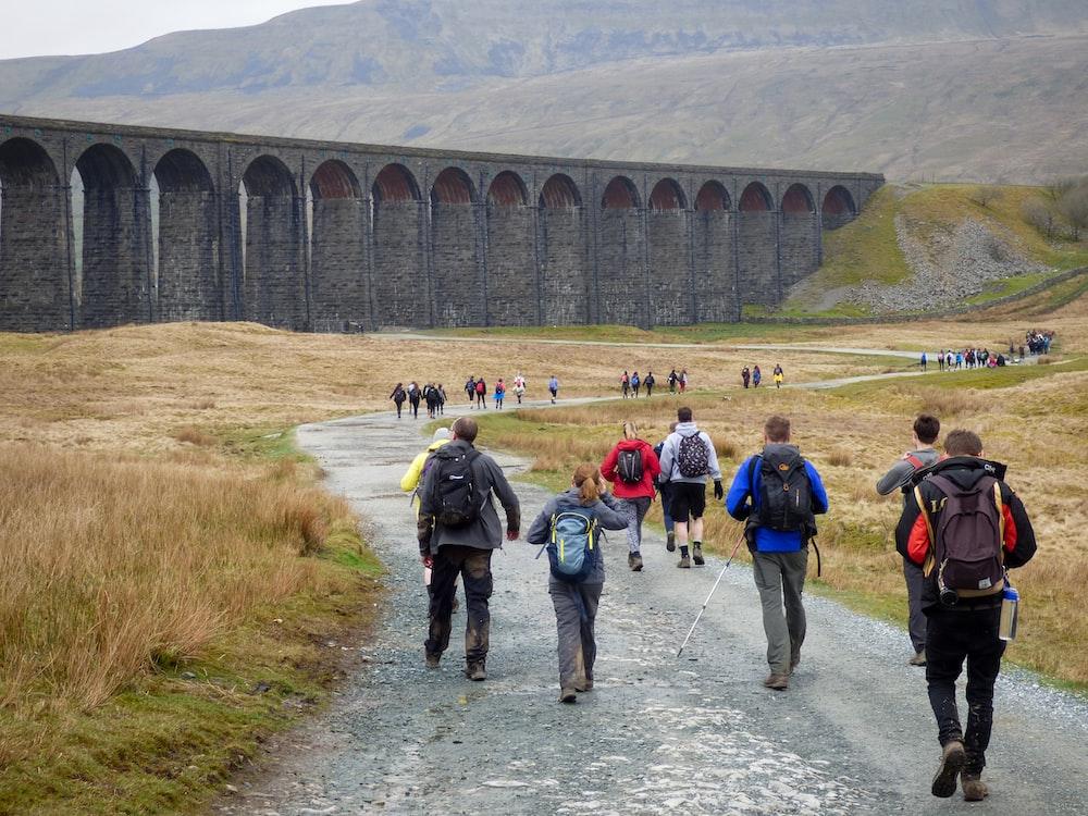 people walking near gray concrete bridge during daytime