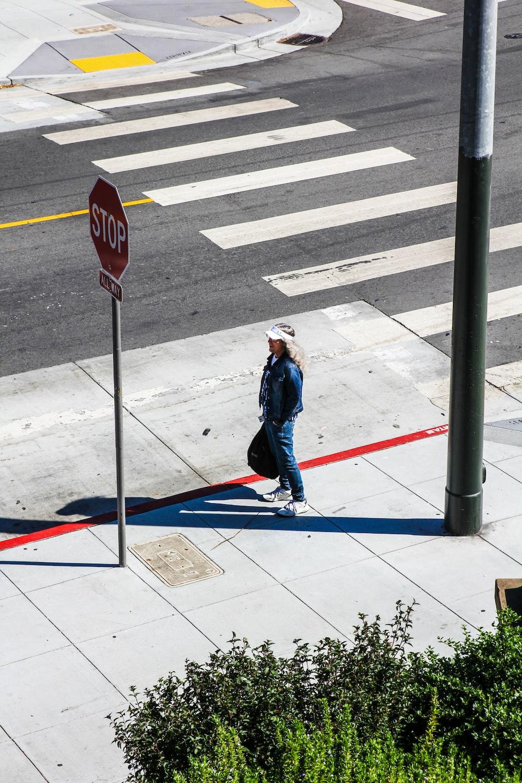 woman walking on sidewalk during daytime