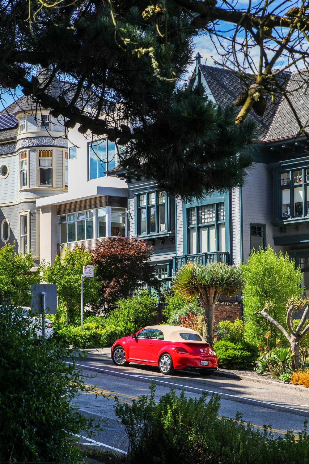 red coupe parking near house during daytime