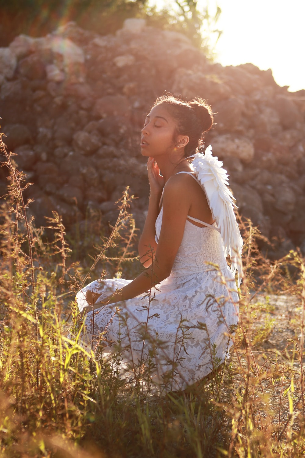 woman wearing white spaghetti strap dress with wings touching her neck while sitting near green field during daytime