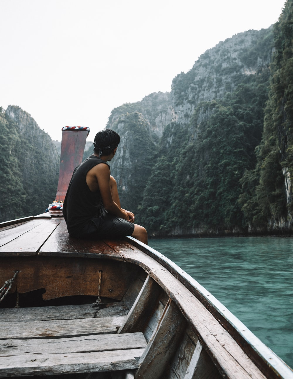 man sitting on brown wooden boat in body of water during daytime