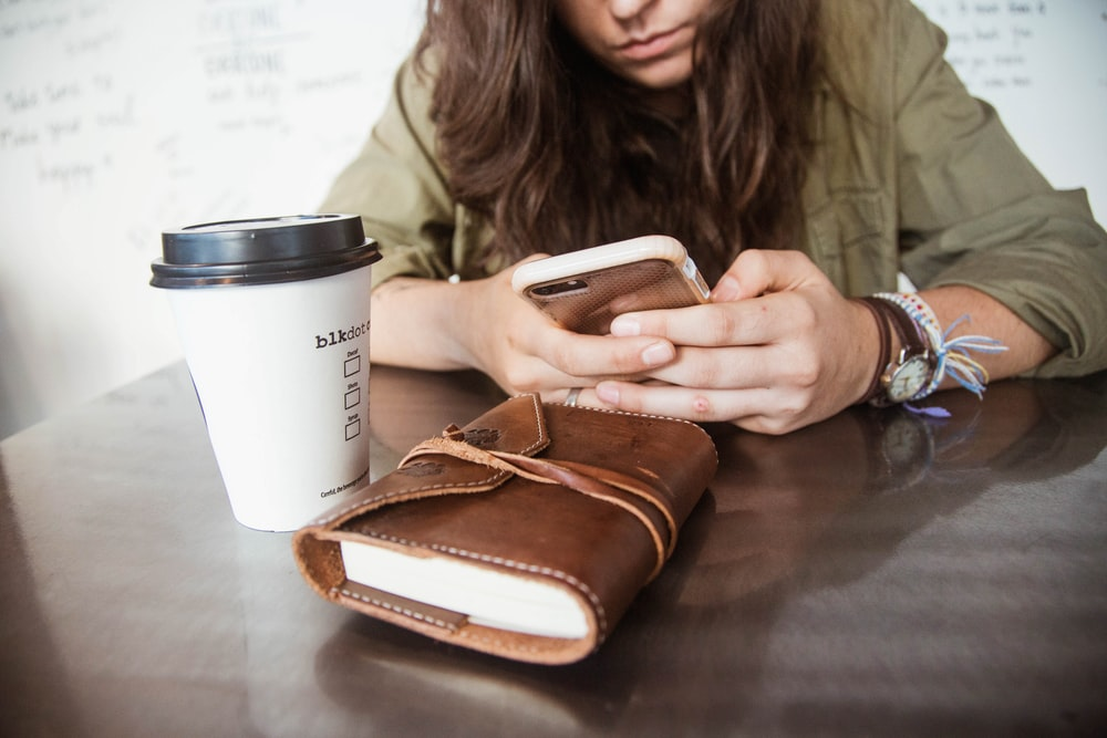 woman sitting at the table while using smartphone