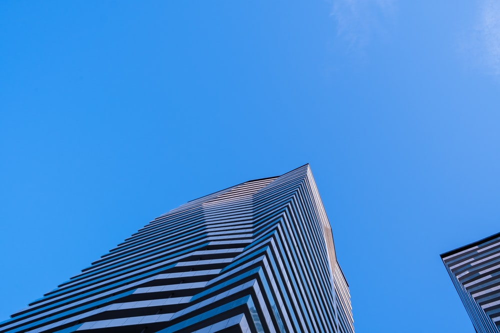 low-angle photography of blue high-rise building