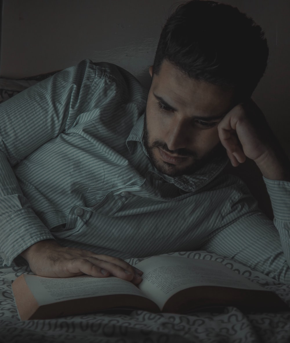 man reading book while lying on bed