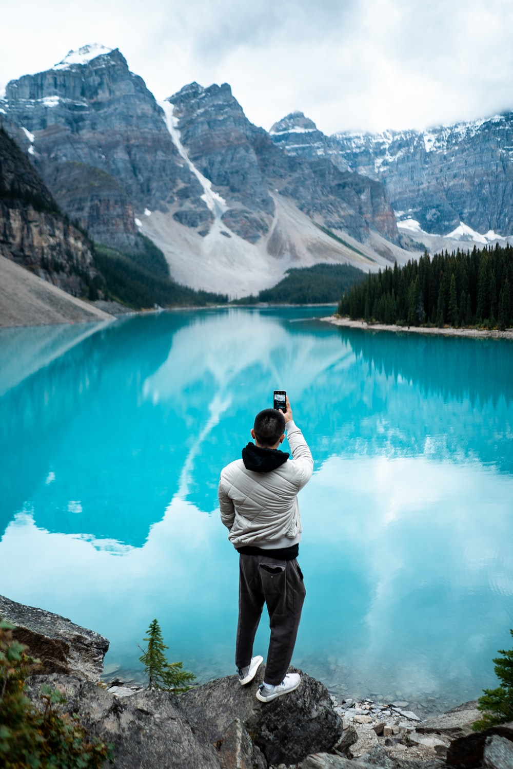 man standing on Moraine Lake during daytime
