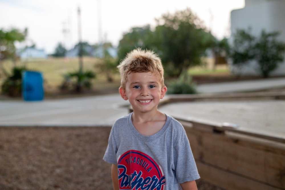 selective focus photography of smiling boy in gray shirt during daytime