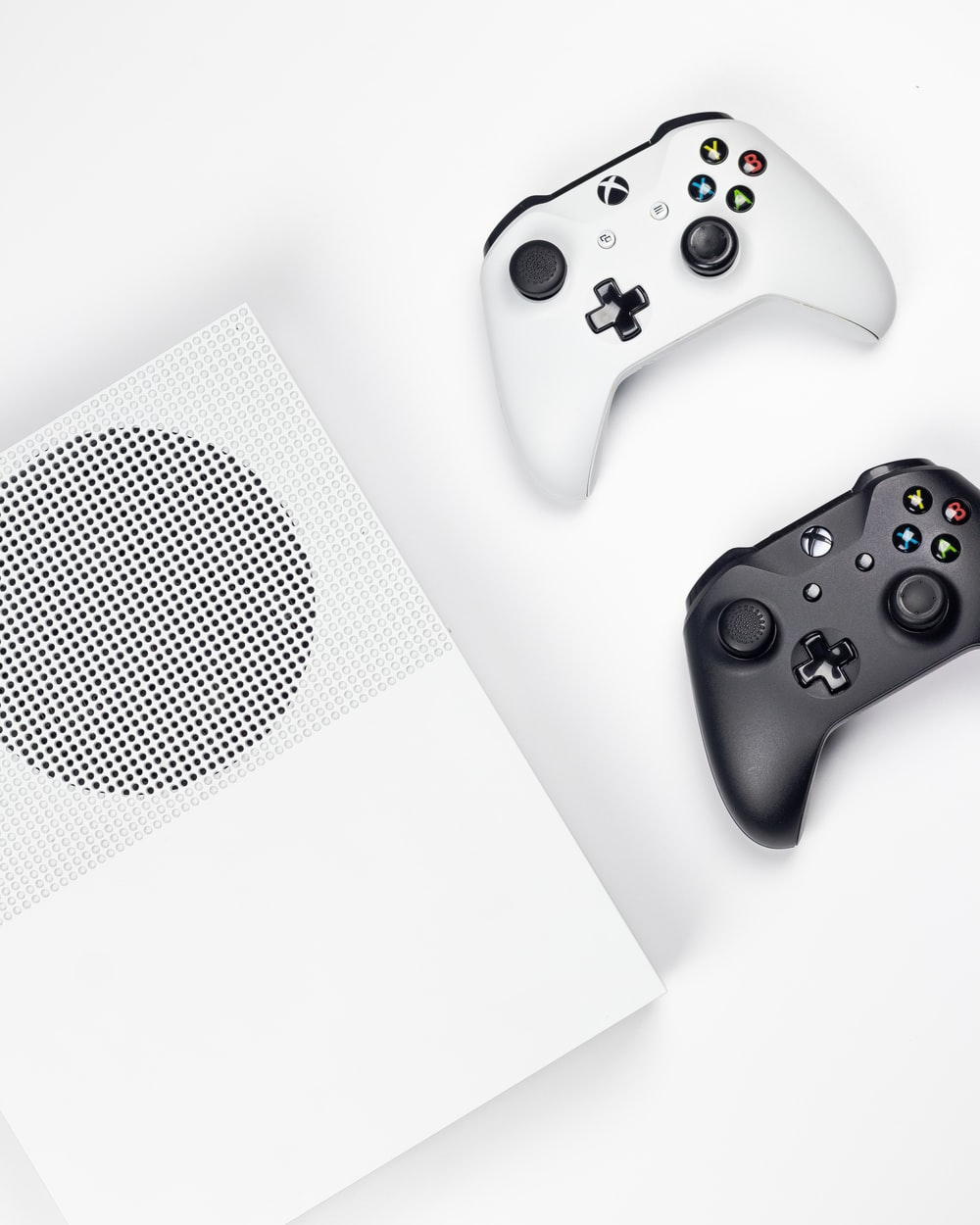 white Xbox One and two black and white game controllers on white background
