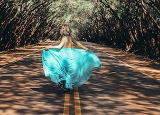 woman wearing teal backless dress walking on asphalt road