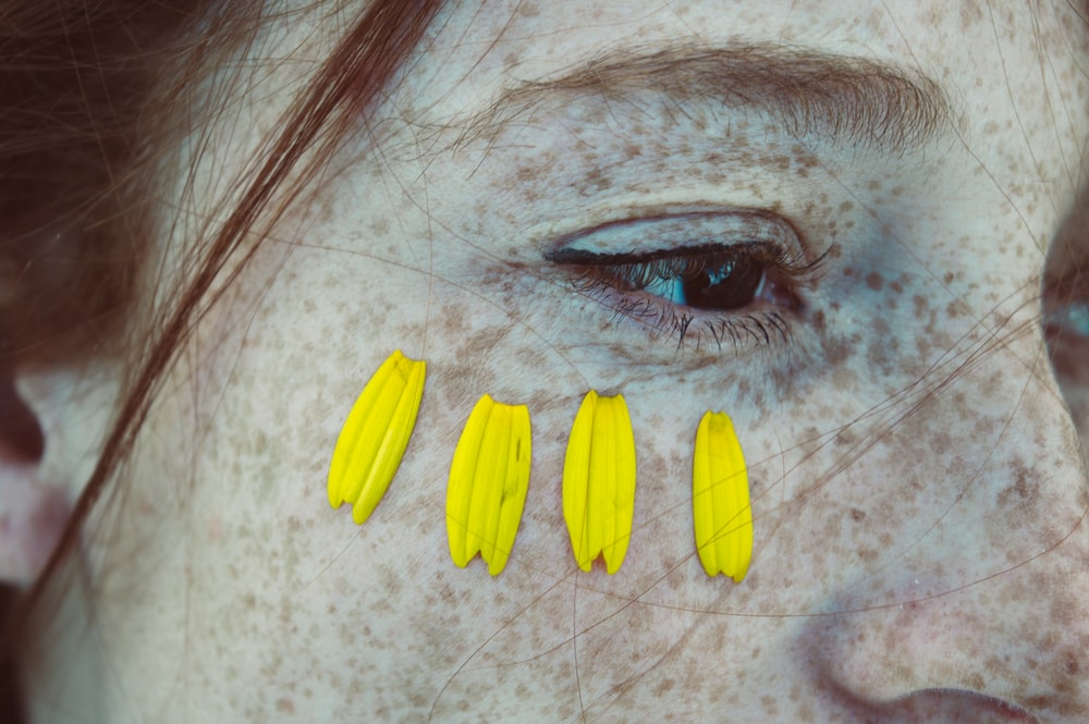 close view of woman's face with four yellow petals