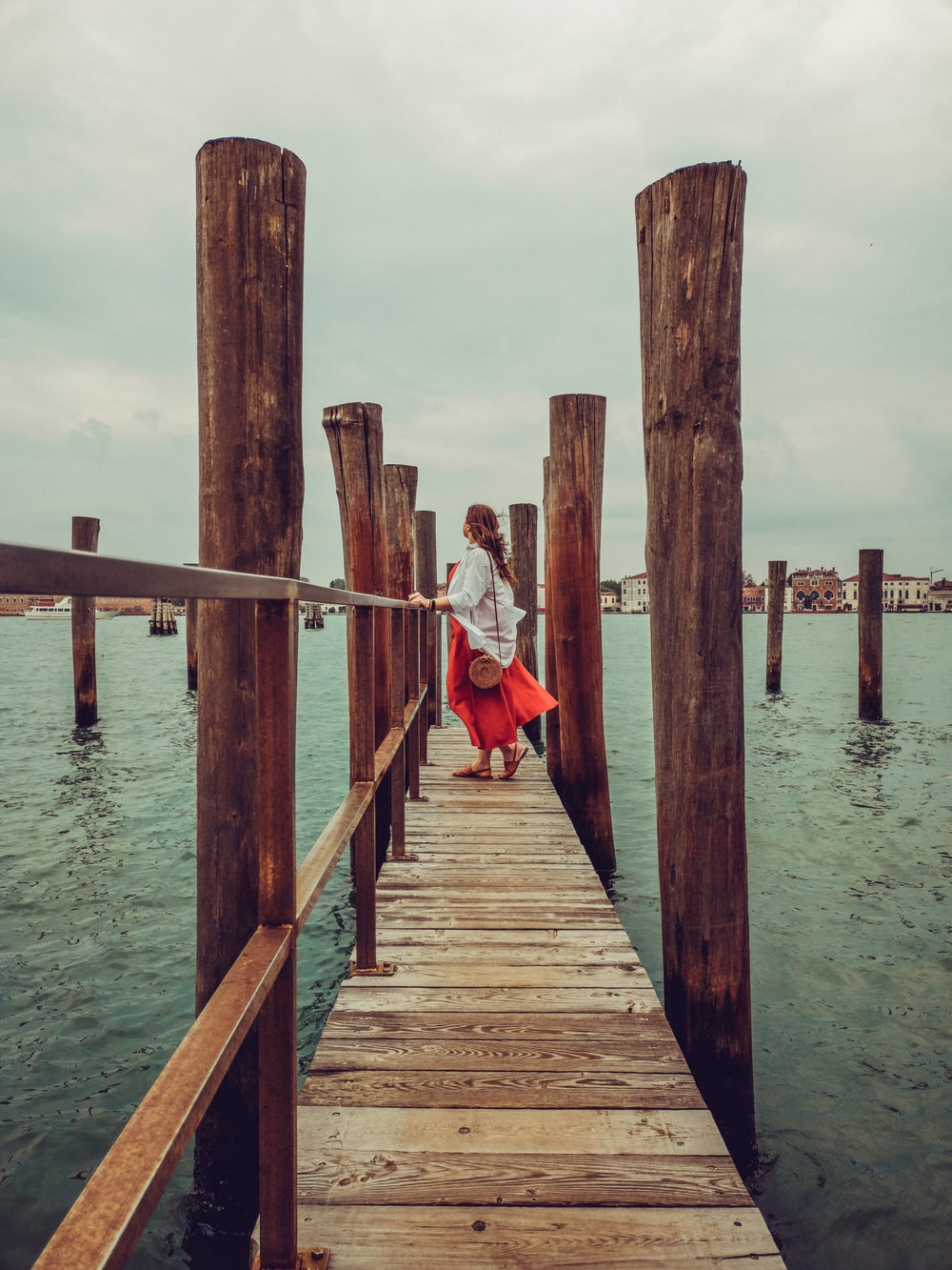 woman standing on brown wooden dock during daytime