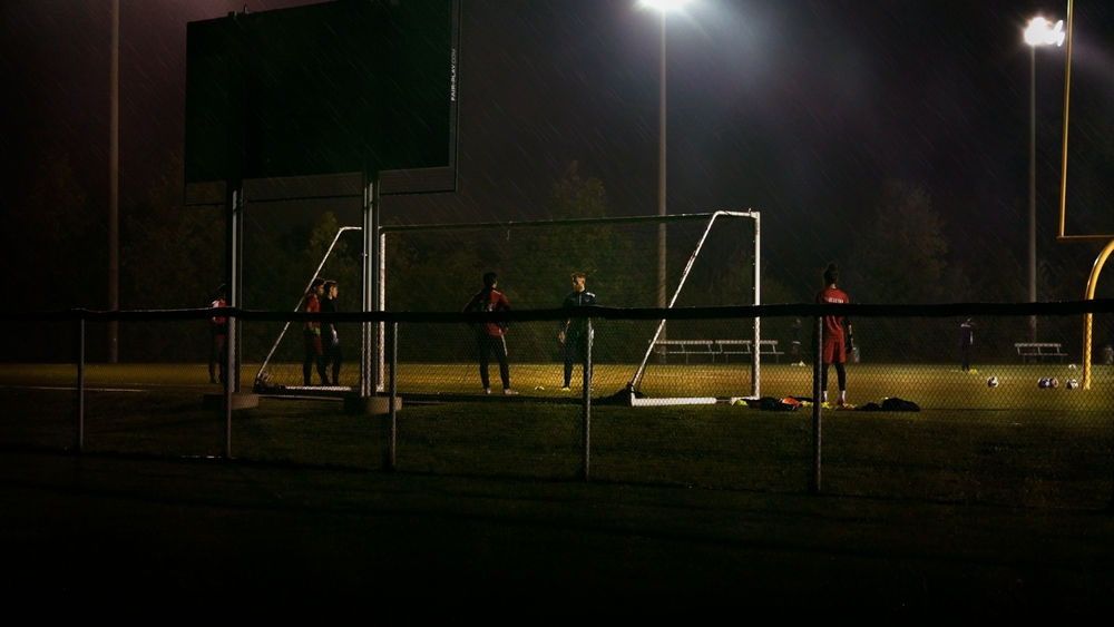 men plays soccer during nighttime