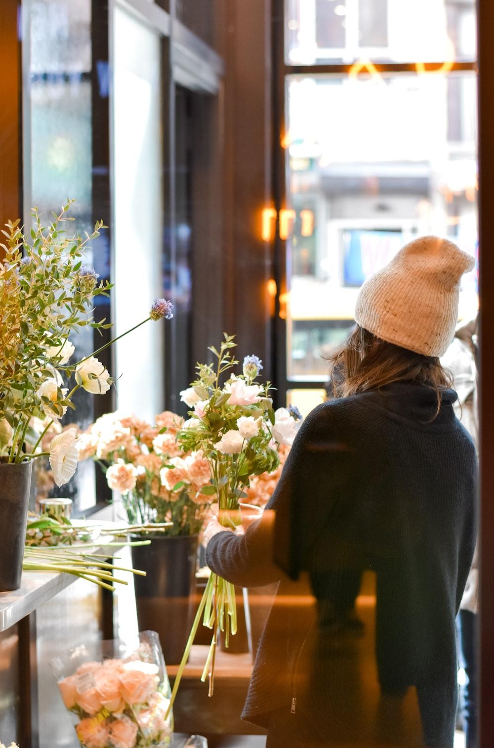 woman arranges white petaled flowers