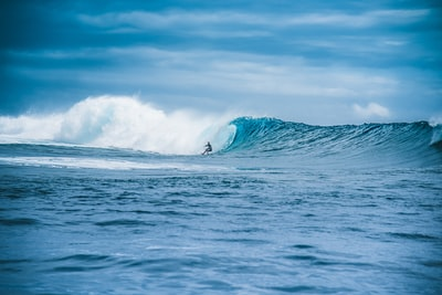 man surfing on sea waves during daytime tahiti teams background