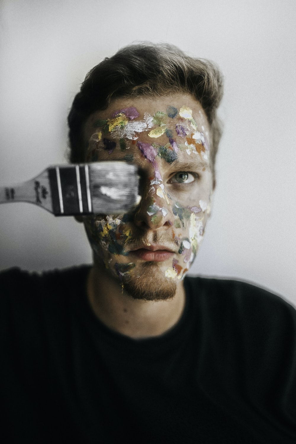 man wearing black shirt with paint on his face with paintbrush covering his right eye