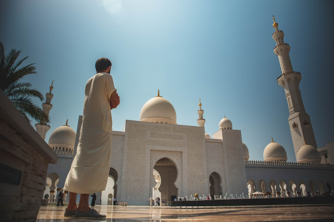 A wide shot of a person wearing white thawb standing at Sheikh Zayed Grand Mosque Center in Abu Dhabi