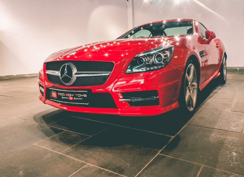 red Mercedes-Benz coupe near wall