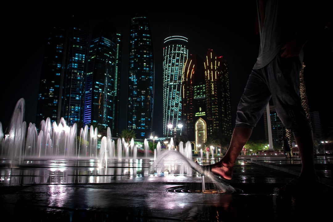 A low angle shot of a barefoot person walking on groundwater fountains near Etihad Towers at night
