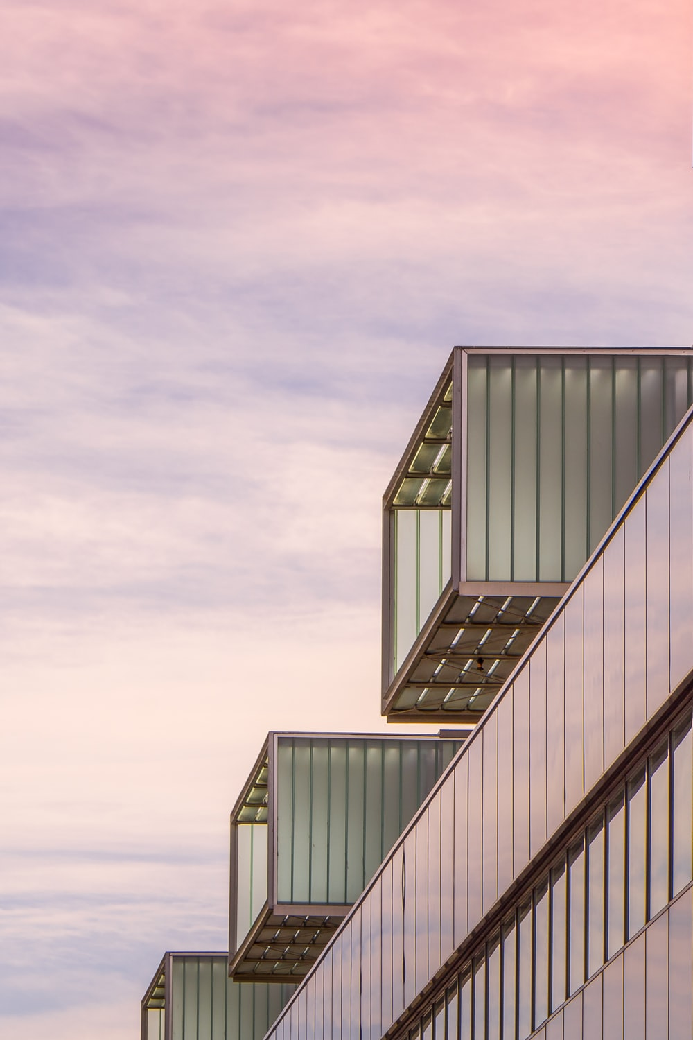 low-angle photography of a multi-storey building under a cloudy sky