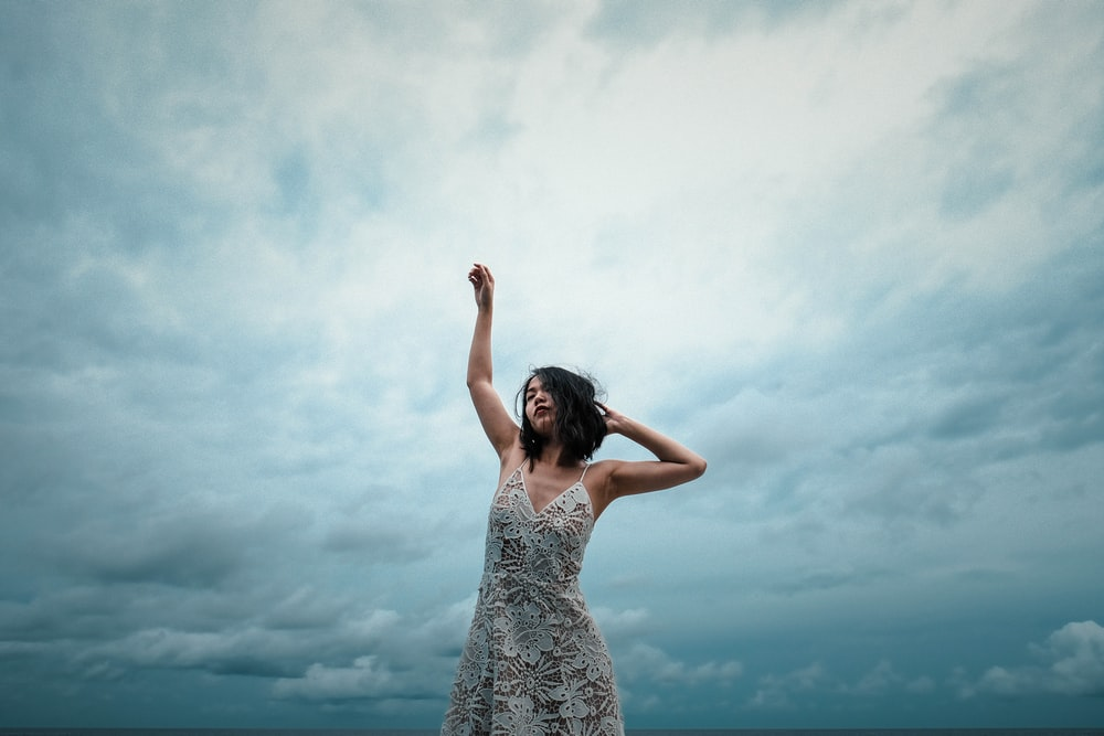 woman wearing white floral dress raising right hand