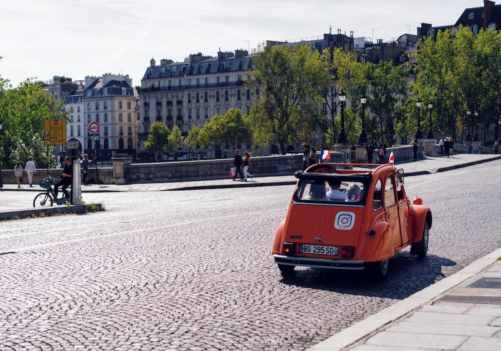 orange vehicle running on park