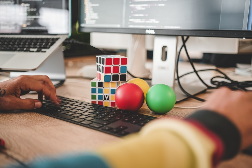 person using computer and two Rubik's Cube near monitor