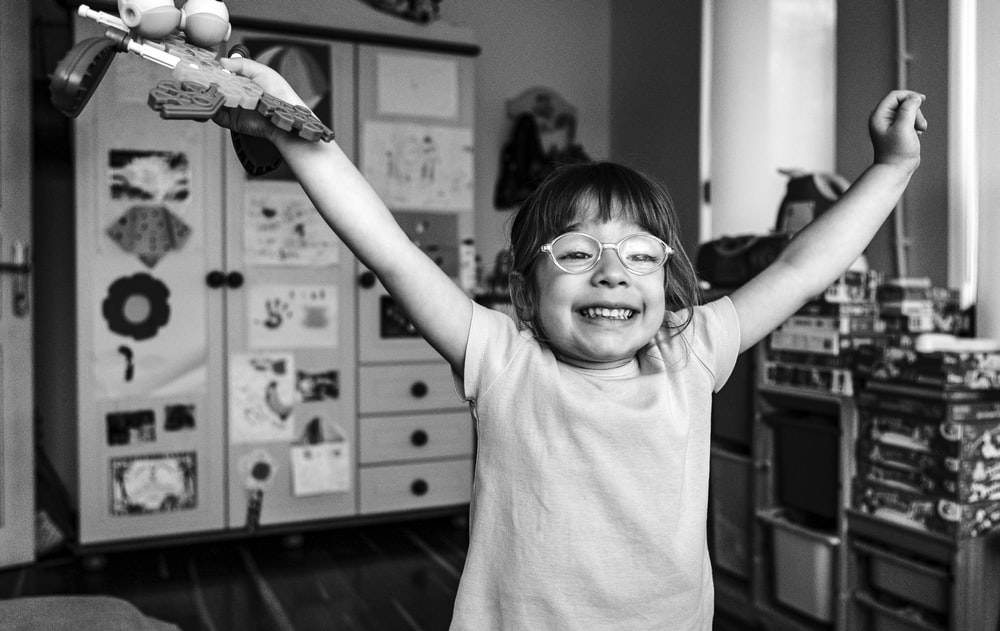 grayscale photography of girl raising both hands smiling