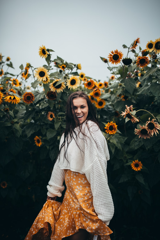 smiling woman standing beside black-eyed Susan flower field during daytime