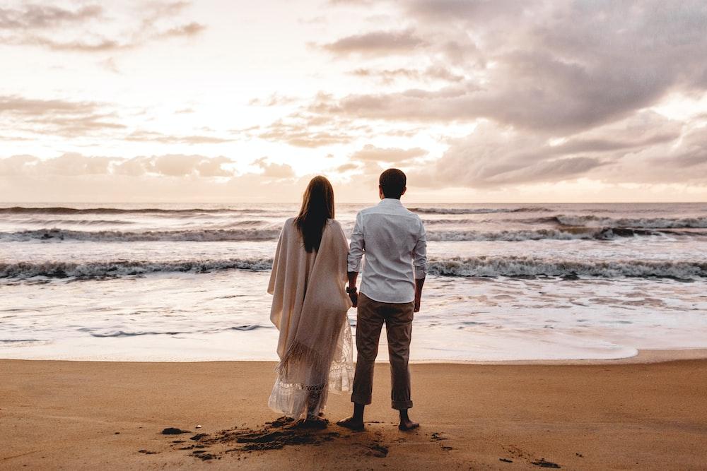 woman wearing beige dress and man wearing white dress shirt standing on seashore