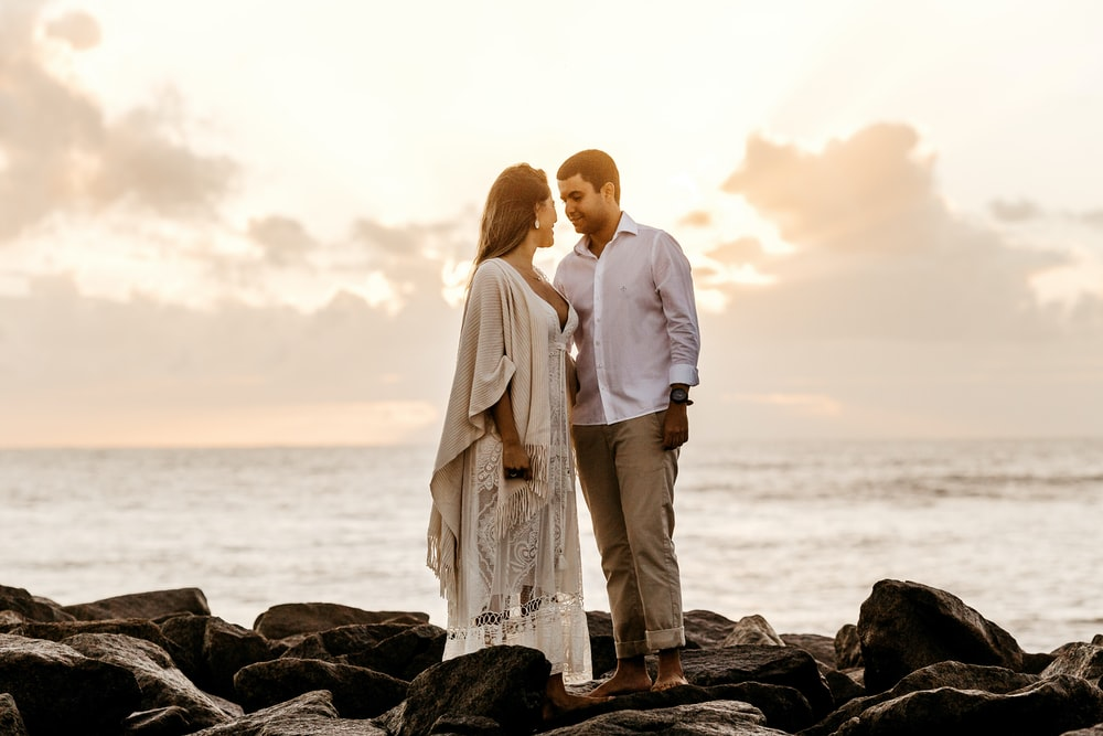 man and woman facing beside each other standing on rocky shore during day