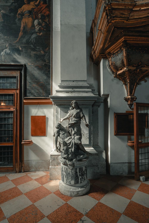 statue beside pillar indoors