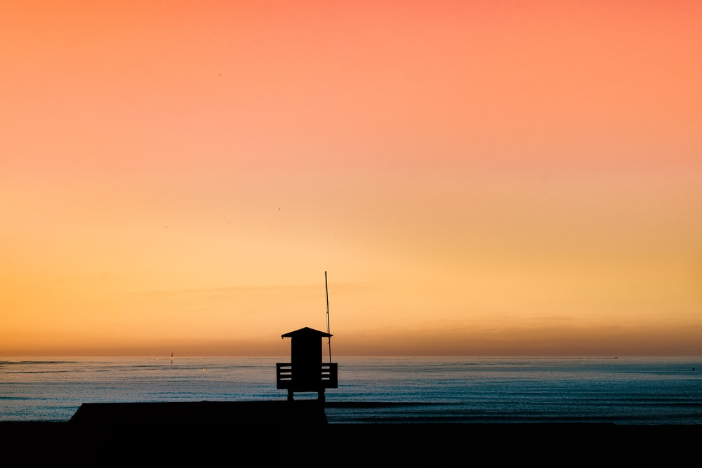 silhouette photography of a cottage by the sea during golden hour