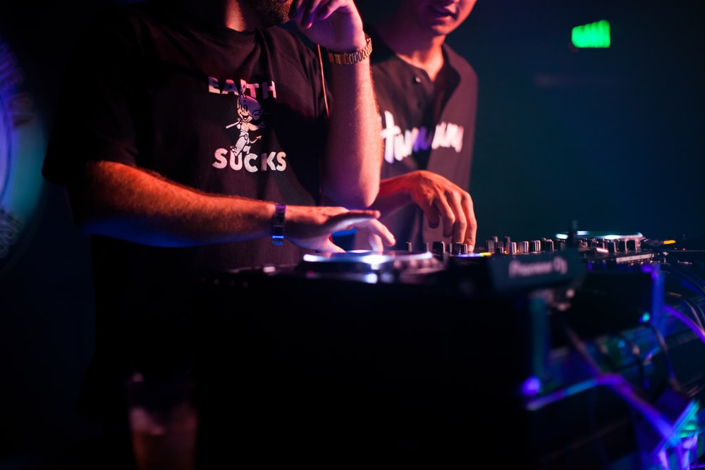 two men playing DJ controllers