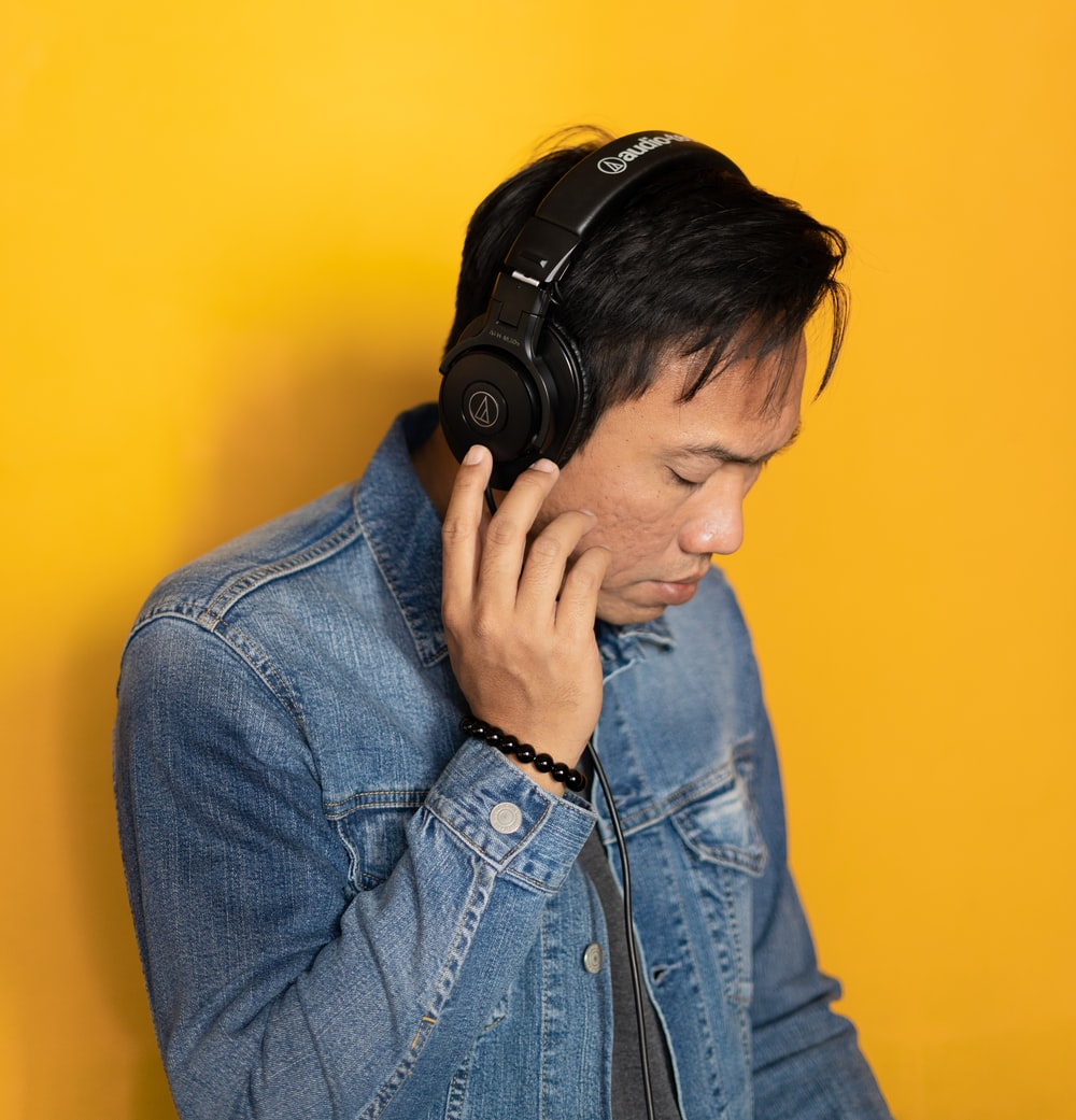 man wearing black wireless headphones and denim jacket