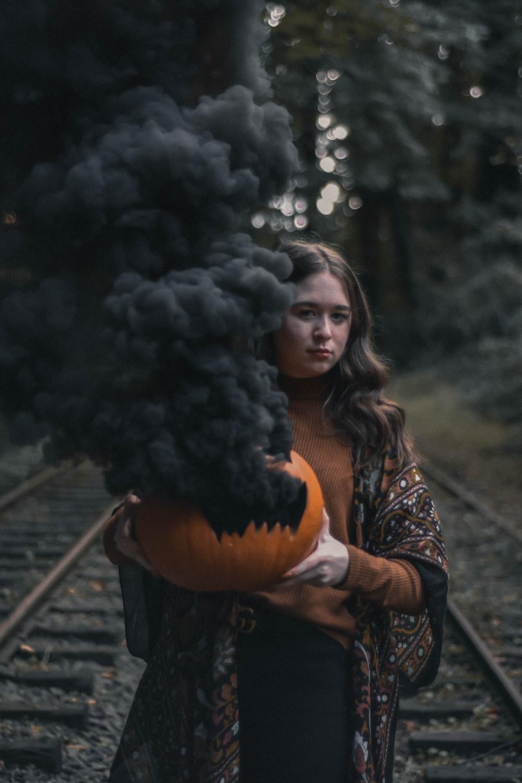 woman holding orange pumpkn