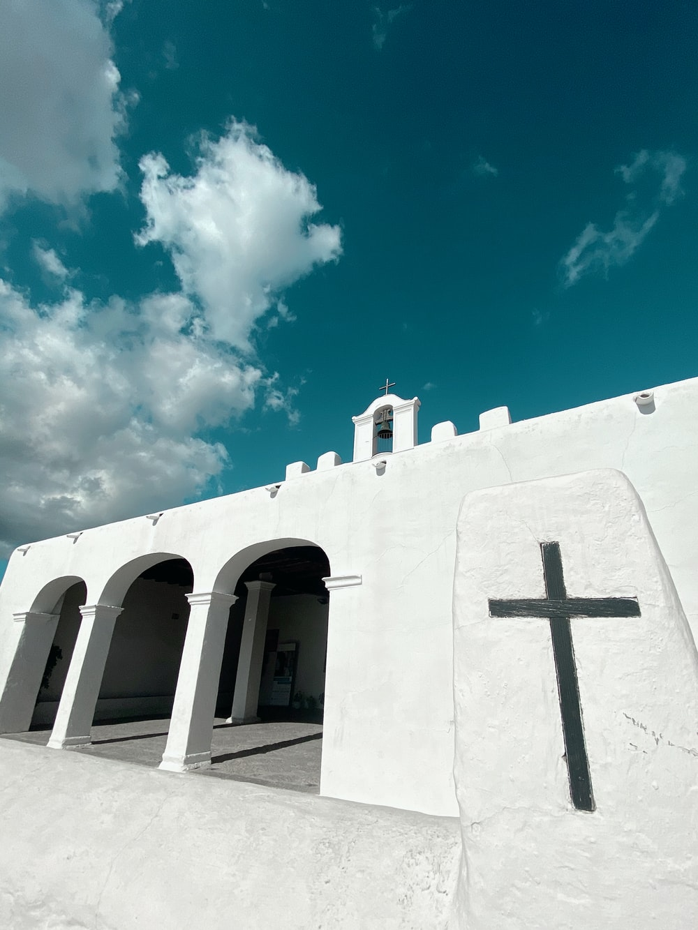 low-angle photography of a white cathedral under a blue sky