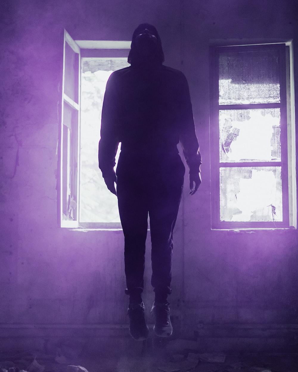 man in black pants beside window