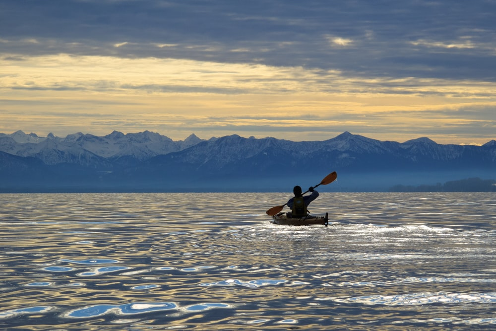 silhouette photo of man riding on kayak