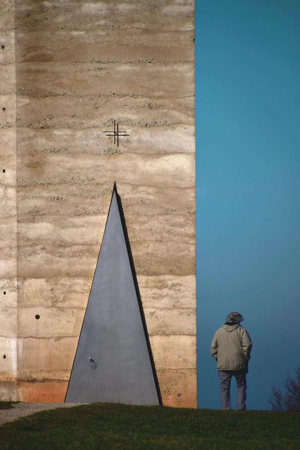 person wearing white hooded jacket standing near concrete wall